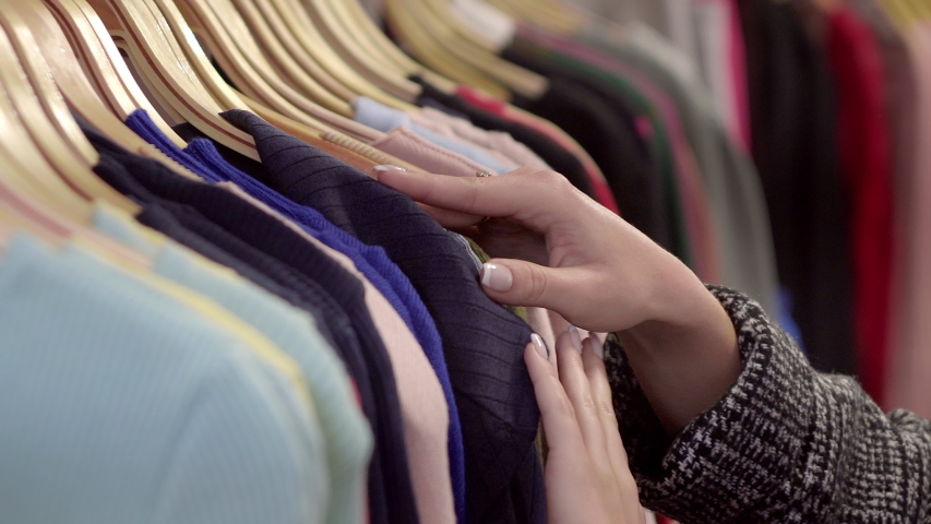 Close-up of female hands plucked a hanger with clothes. Woman's hands run across a rack of clothes. Dolly shot from the side. Woman's hand smoothing a colorful clothes. Close-up: a hanger for clothing