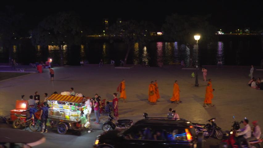 phnom penh , kandal / Cambodia - 01 07 2018: Buddhist monks walking along riverside at night in Phnom Penh, Cambodia
