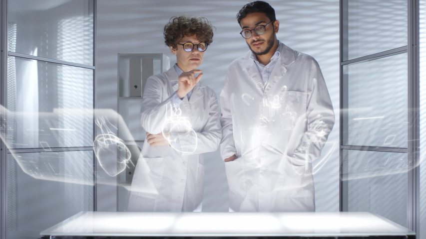 Male and female doctors in lab coats using futuristic computer with 3D hologram interface and discussing human heart projected in the air Royalty-Free Stock Footage #1035210764