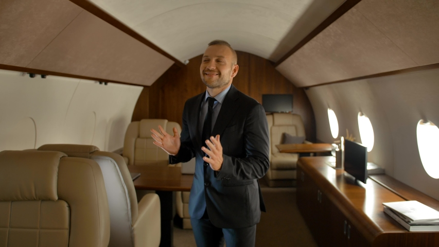 Rich business man dancing inside of luxury jet. Entrepreneur extremely happy of comfortable first class aircraft flight. Royalty-Free Stock Footage #1035212327