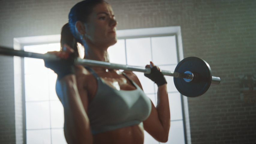 Athletic Beautiful Woman Does Overhead Deadlift with a Barbell in the Gym. Gorgeous Female Professional Bodybuilder Workout Weight Lift Exercises in the Authentic Fit Training Facility. Zoom in | Shutterstock HD Video #1035217655