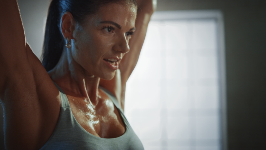Athletic Beautiful Woman Does Overhead Lift with a Barbell in the Gym. Gorgeous Female Professional Bodybuilder Does Weight Lift Workout Exercises in the Hardcore Training Facility. 4K UHD | Shutterstock HD Video #1035217661