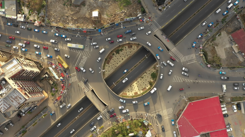 Overhead drone shot of traffic driving over roundabout with highway tunnel underneath, infrastructure and transportation in Addis Abba, Ethiopia
