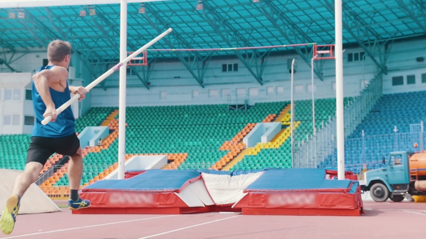 Pole vault training - an athletic man jumping over the bar in the stadium | Shutterstock HD Video #1035233033
