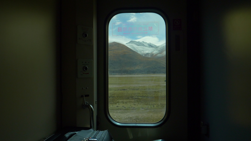 CLOSE UP: Breathtaking view of scenic landscape of Tibet through a small window in the luggage compartment of a sleeper train crossing China. Small window offers a view of snowy Himalaya and plains. | Shutterstock HD Video #1035233510