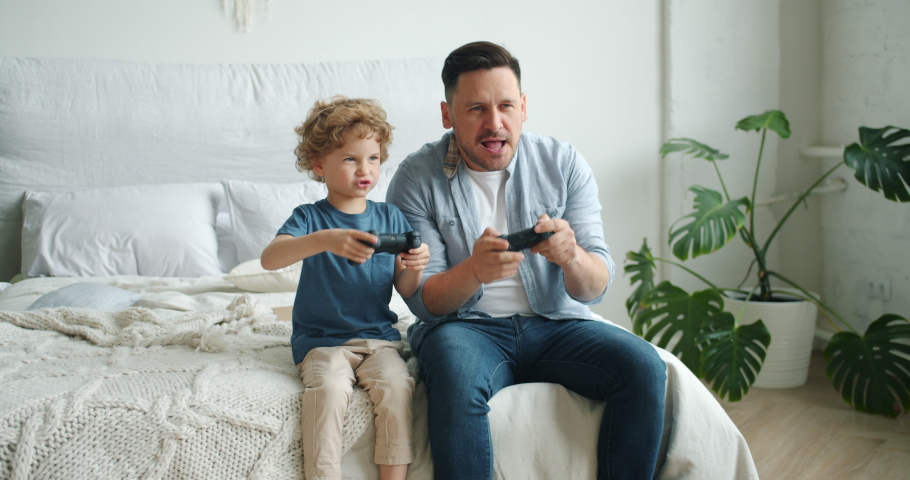 Middle-aged guy father is playing video game with happy child adorable boy sitting on bed at home enjoying activity. Family, leisure time and hobby concept. #1035238307