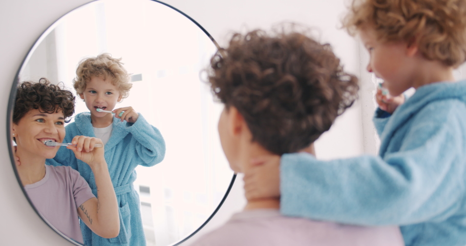 Mother and son happy family brushing teeth in bathroom looking at mirror smiling together enjoying healthcare. Boy is wearing modern bathrobe.