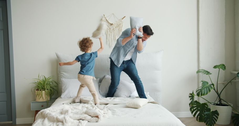 Father and little son are playing on bed fighting pillows laughing falling then mother is coming home walking in bedroom. Family, relationship and games concept. #1035246644