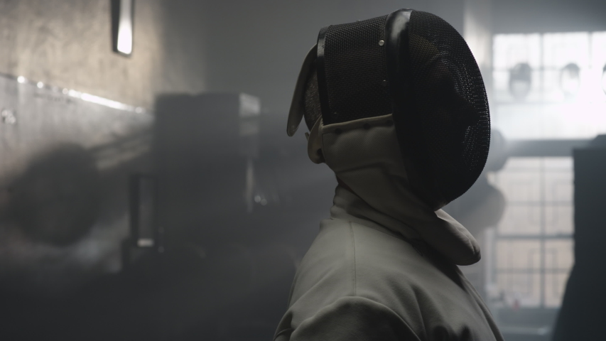 A fencer takes off his fencing mask in a dark and foggy locker room   Shutterstock HD Video #1035247490