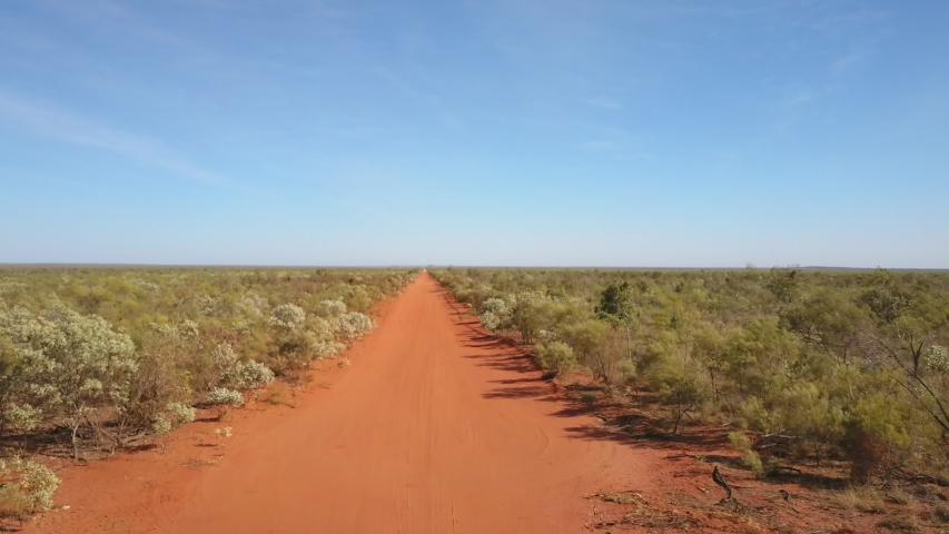 Panoramic aerial view of flight above straight red dirt track in outback Australia, with road, leading to horizon, green bush, sunny blue sky as background. | Shutterstock HD Video #1035254402