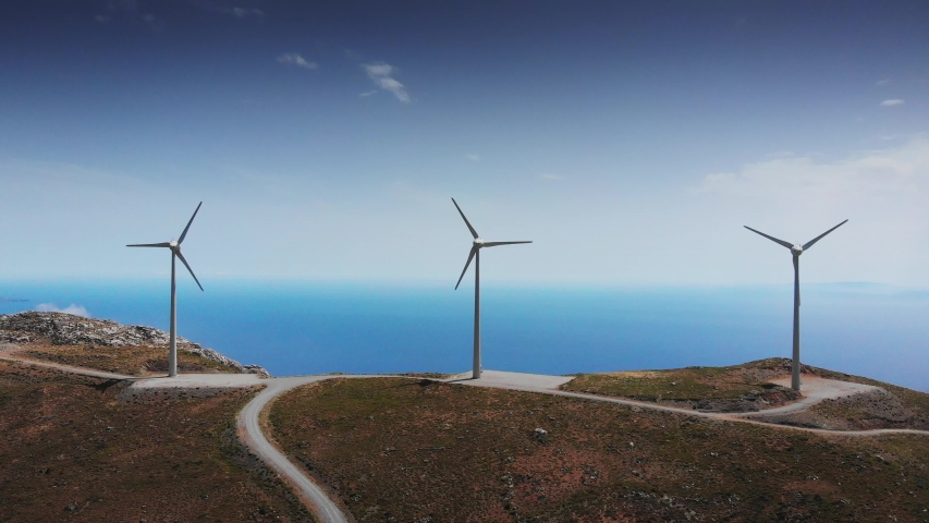 Wind turbines in motion on mountain peak by Mediterranean sea, Crete, Greece | Shutterstock HD Video #1035258896