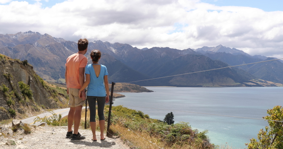New Zealand travel adventure couple stopping at view point looking at mountains and amazing nature landscape of Wanaka lake. 59.94 FPS slow motion. | Shutterstock HD Video #1035260675