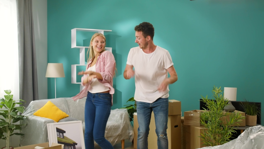 Young couple have fun dancing in their new home #1035267707
