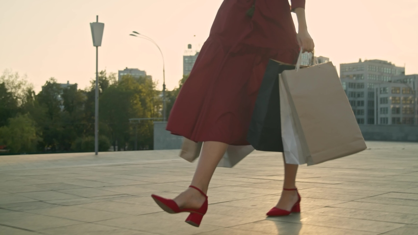 Young woman in red dress with shopping bags walks on the street during sunset