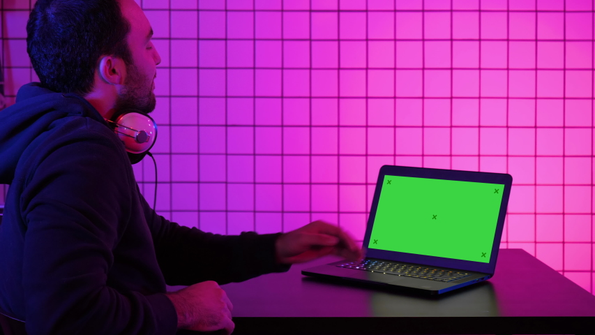 A young cheerful gamer smiling to the camera and looking at laptop. Green Screen Mock-up Display. Royalty-Free Stock Footage #1035269333