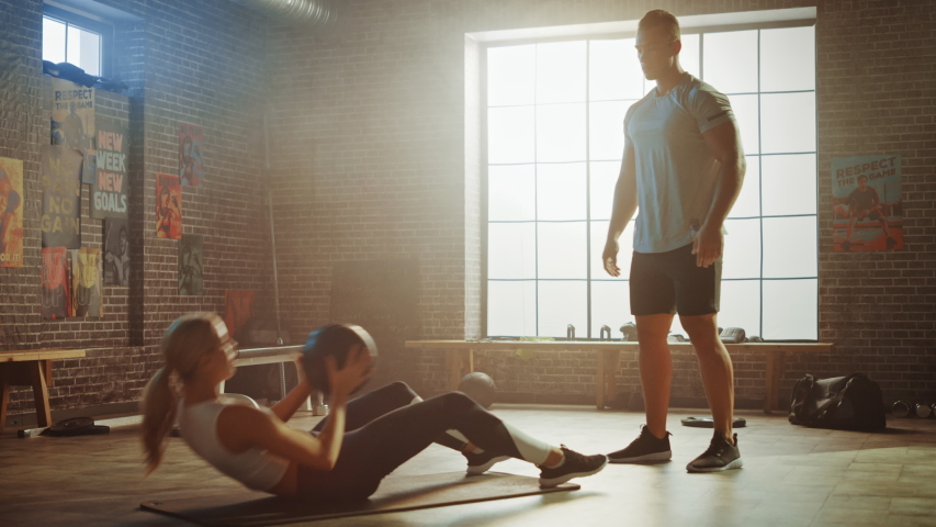Beautiful Young Girl Exercises with Personal Trainer, Doing Sit-ups with Medicine Ball, Throwing Pass Back and Forth. Fit and Strong Couple Workout. Exercising Strength, Cardio and Power