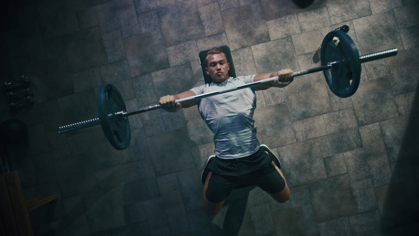 Top View of Professional Athlete Doing Bench Press Workout with a Barbell in the Hardcore Gym. Muscular and Athletic Bodybuilder Doing Barbell Exercise. Zoom Out Royalty-Free Stock Footage #1035271574