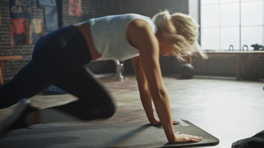 Beautiful and Young Girl Does Running Plank on Her Fitness Mat. Athletic Woman Does Mountain Climber Workout in Stylish Hardcore Gym | Shutterstock HD Video #1035271577
