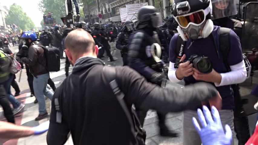 Paris / France - 05 01 2019: Slow motion of riot police pushing protestors and press away with shields