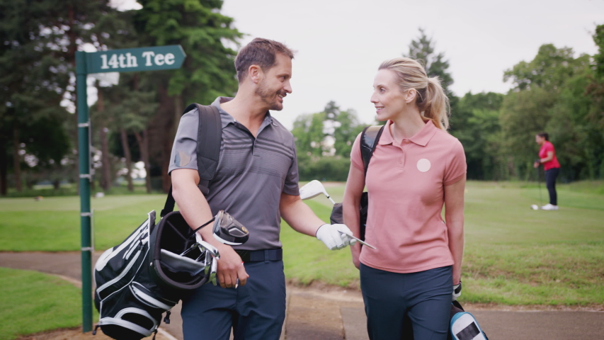 Mature Couple Playing Golf Carrying Golf Bag And Talking