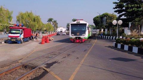 Jogjakarta / Indonesia - July 3rd, 2019: Establish Shot of Railroad Crossing in Front of Tugu Station