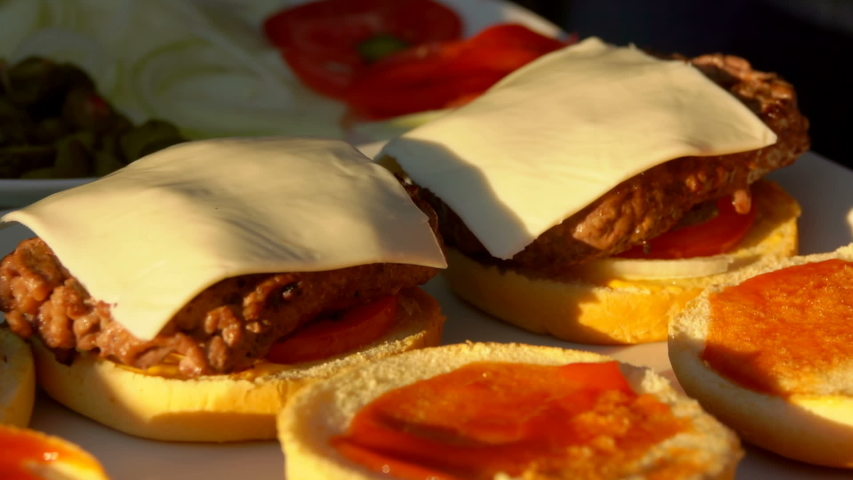 Sesame buns are laid out on top on a delicious hamburger with cheese and tomatoes on a white plate | Shutterstock HD Video #1035281180