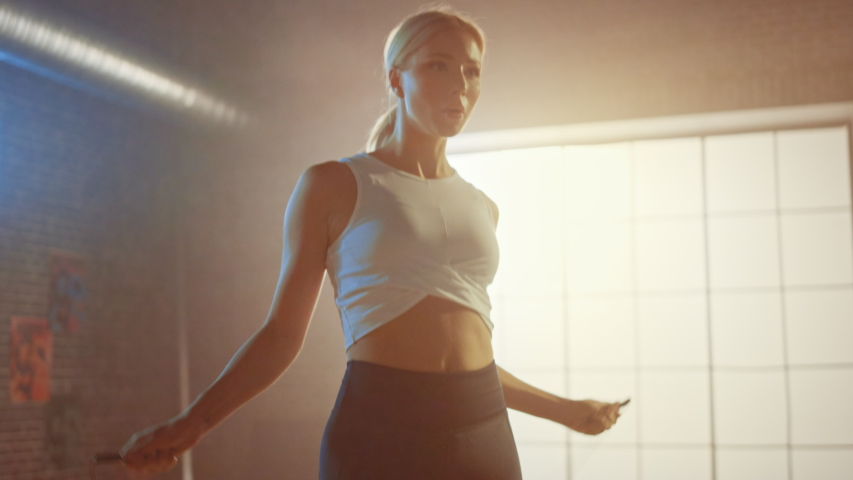 Fit Athletic Blond Woman Exercises with Jumping Rope in a Loft Style Gym. She Does Her Intense Cross Fitness Training Program. Facility has Motivational Posters on the Wall. Slow Motion Portrait. Royalty-Free Stock Footage #1035281891
