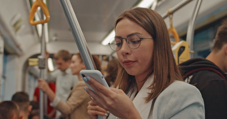 Public transport. Attractive young girl in public transport using smartphone chatting and texting with friends. Cute woman holds the handrail, while travelling on tram. City, urban, transportation.   Shutterstock HD Video #1035290861