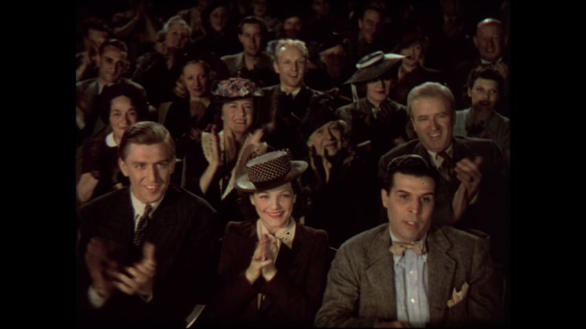1930s: Audience sits in theater, claps. Man stands on stage behind podium, talks. Woman walks over to podium, reads from paper.
