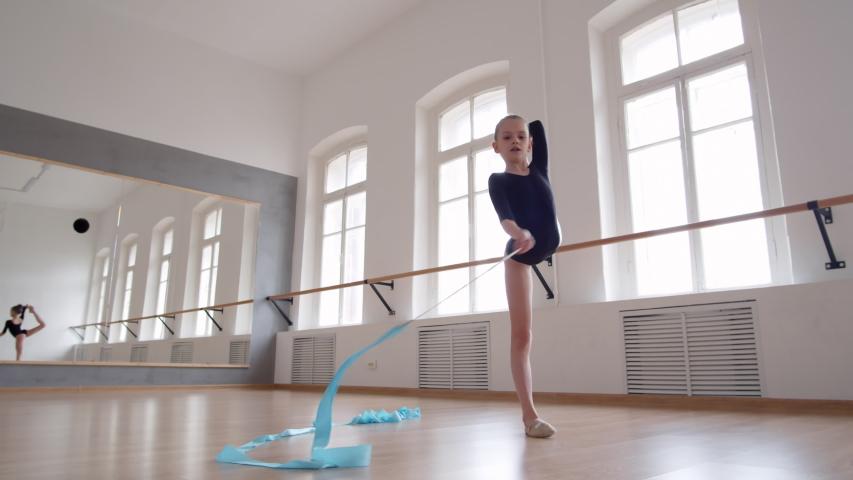 Wide shot of Caucasian female dancer wearing black leotard exercising with blue ribbon in studio #1035305444