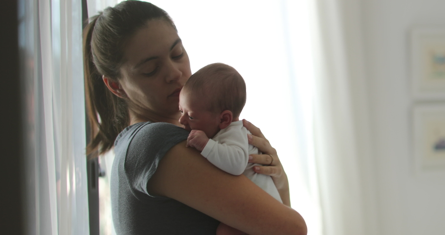 Candid mom holding newborn baby hugging and loving