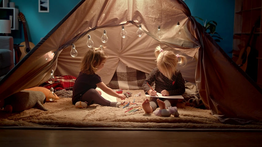 Two little sisters draw with pencils in a decorative tent in the room. | Shutterstock HD Video #1035312794