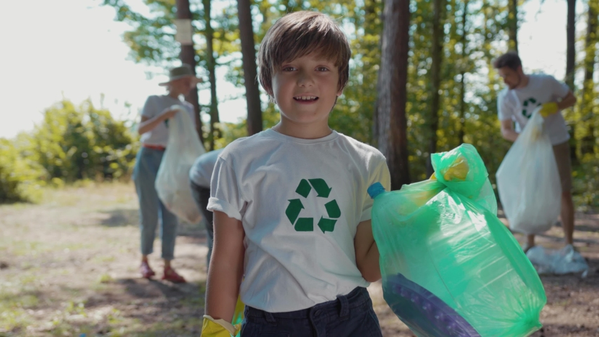 Happy boy voluteers activists child in gloves tidying up rubbish in park or forest look at camera smile