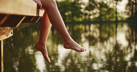 Woman relaxes by the lake sitting on the edge of a wooden jetty , swing one's feet near the water surface. Sunny joyful summer day or evening concept. 4K, DCi resolution, slow motion.
