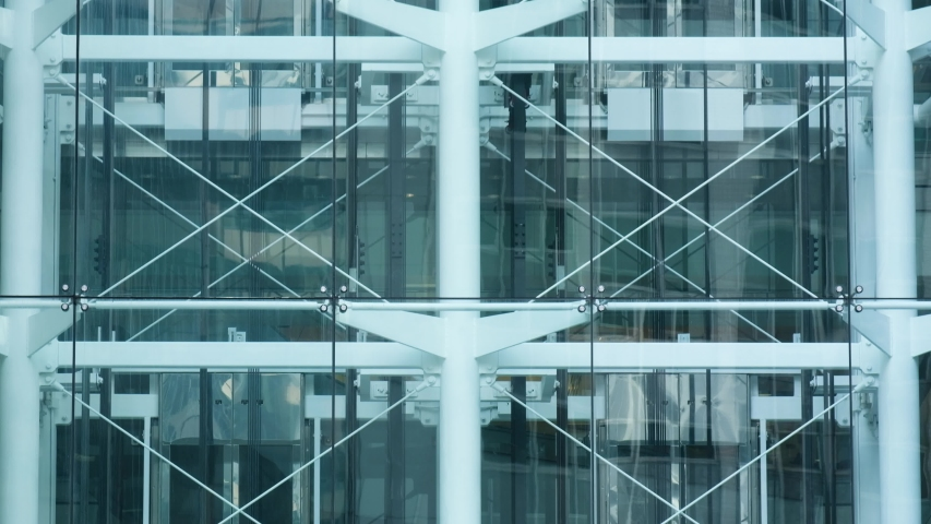Glass elevators outside the skyscraper building, business architecture. Tilt shot. Royalty-Free Stock Footage #1035343103