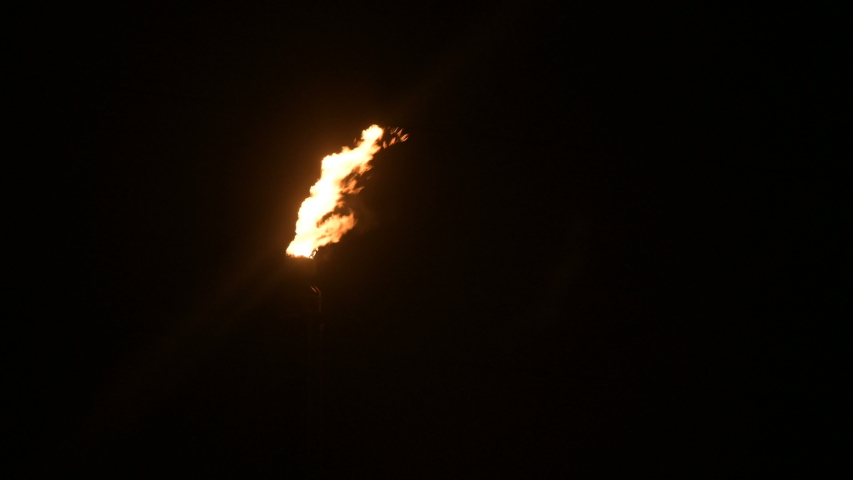A night shot of a flaming gas torch of petrochemical production in complete darkness. Low key oil combustion and environmental pollution. Ecology problems concept   Shutterstock HD Video #1035348638