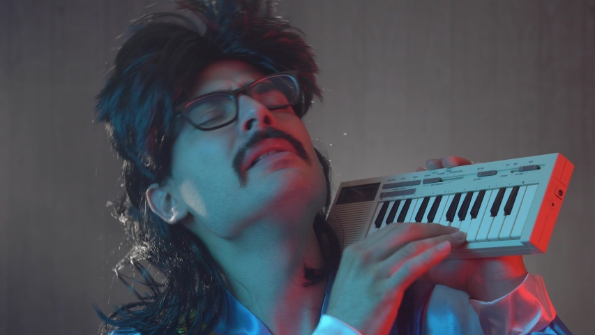 Man with mustache and mullet from the 70s 80s 90 playing on his retro synth keyboard. Vintage concept.