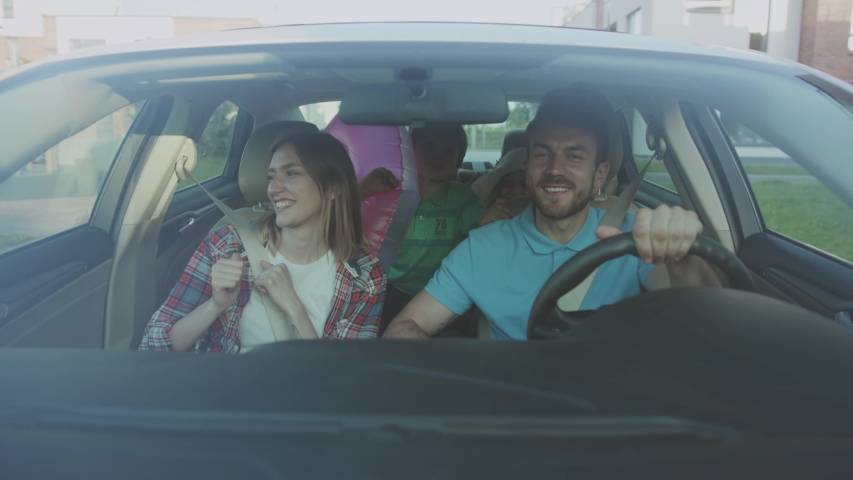 NEW YORK - June 10, 2018: Amazing young family roadtrip to the sea in summer. Front view of joyful parents and kids dancing and singing a song riding a car through modern city at daytime. | Shutterstock HD Video #1035354818