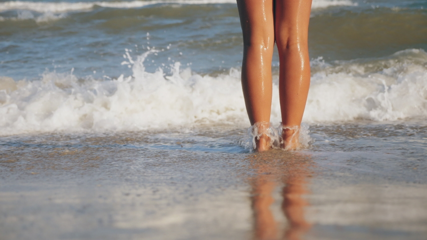 Close-up legs of an unknown tanned girl stand in a sandy beach in refreshing seawater. Girl feet washed by sea waves. Slow-motion | Shutterstock HD Video #1035355304