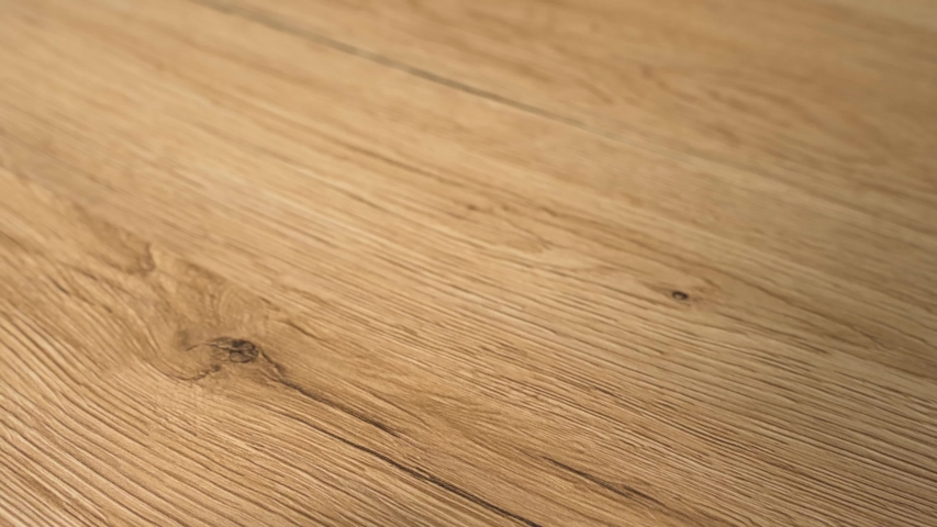 Closeup of the wood floor newly installed. Floor is made of the natural oak hard wood and sanded and finished with natural clear flooring stain. Home improvement and remodel concept in slow motion. #1035359798