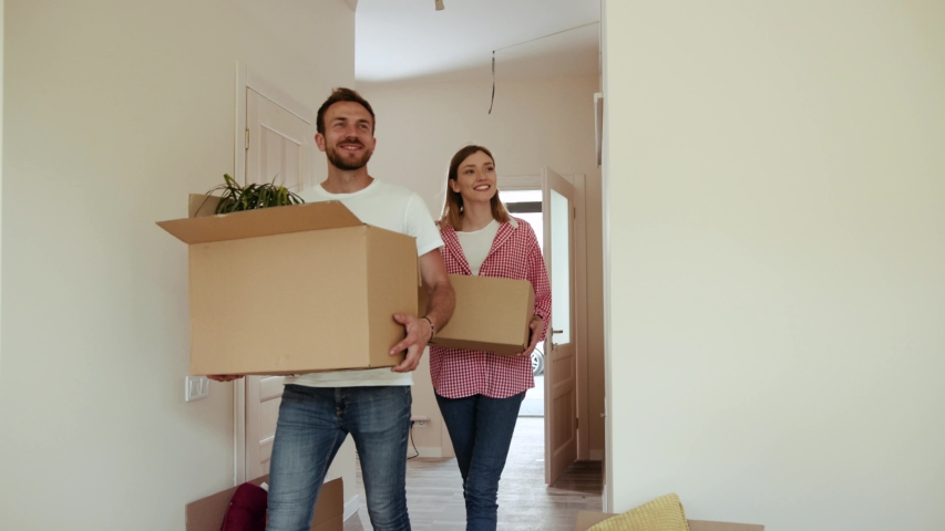 Moving to new apartment of young couple in love smiling friendly coziness home optimistic moment floor box family indoor lifestyle room together amazing funny happiness slow motion | Shutterstock HD Video #1035365981