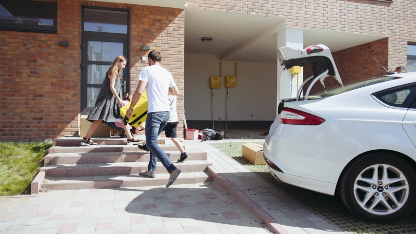 Near new house happy family get out from the car and unload boxes to adults moving to a new apartment in a lovely area on a sunny day baggage arrive siblings close up slow motion
