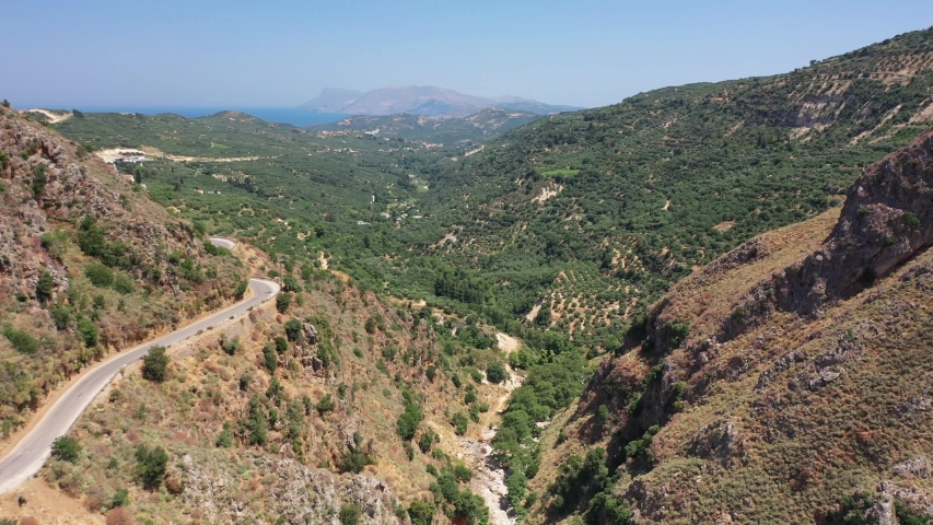 Aerial bird's-eye view video from drone of flight from Topolia Gorge canyon to a mountain valley with olive groves and mountain Topolia village. Kissamos, Chania prefecture, Crete, Greece.