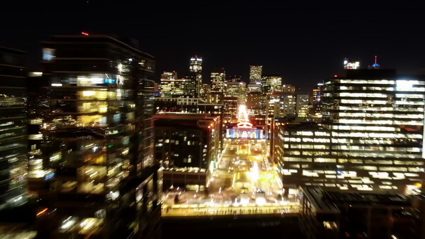 Time Lapse Aerial Forward Along 17th Street in Denver at night with Lit Skyscrapers and Union Station