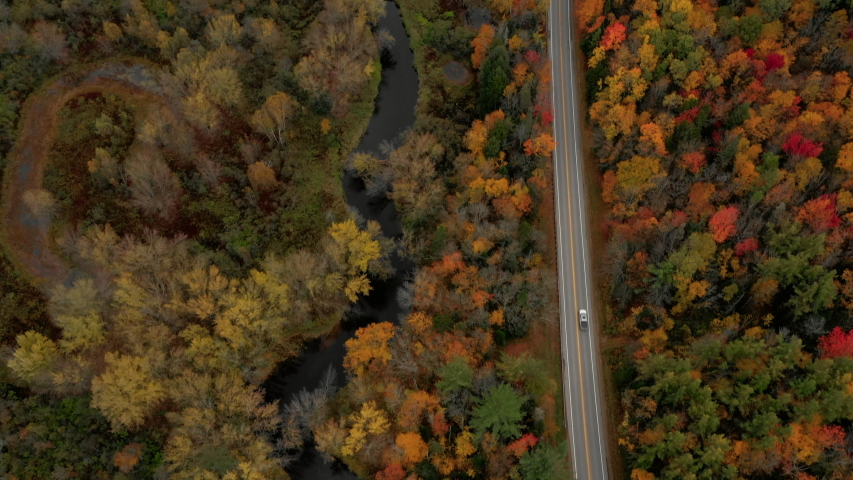 Aerial Pan Up: Car Driving On Road Through Brightly Colored, Forest Covered Plain - Dixville Notch, New Hampshire