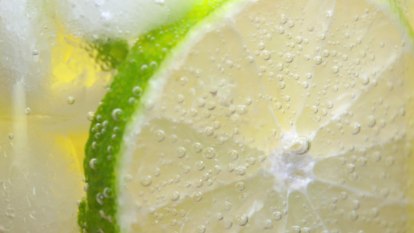 Macro Close-up Glass of cold fizzy refreshing drink with lime slices. Soda with Ice in glass. 360 rotation. 4K UHD video footage | Shutterstock HD Video #1035386729