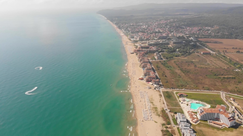 Aerial footage of the beautiful small town and seaside resort of Obzor in Bulgaria showing the coastal hotels and people relaxing and having fun on the golden sunny beaches of the Black Sea coast   Shutterstock HD Video #1035388463