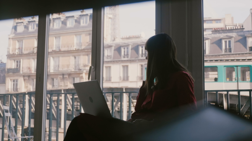 Beautiful focused young businesswoman using laptop, taking phone call at apartment window in Paris, train passing by. | Shutterstock HD Video #1035394205