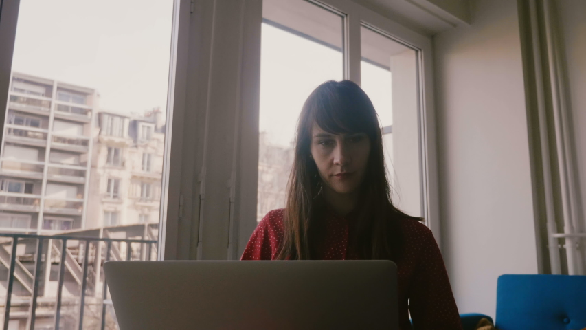 Beautiful focused young businesswoman using laptop and smartphone near apartment window on business trip in Paris. | Shutterstock HD Video #1035394226