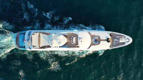 Aerial tracking top down video of luxury yacht cruising in deep blue open ocean sea